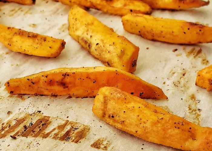Baked sweet potato fries in a pan.
