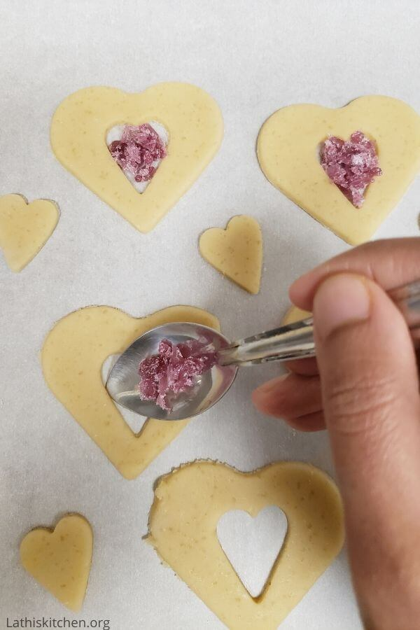 Heart shaped cookies filled with crushed candies.