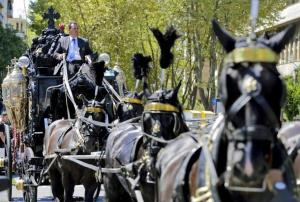 An ornate hearse pulled by six, black-plumed horses, carries the body of Casamonica to a Roman Catholic basilica in the Rome suburbs, where the funeral mass was celebrated