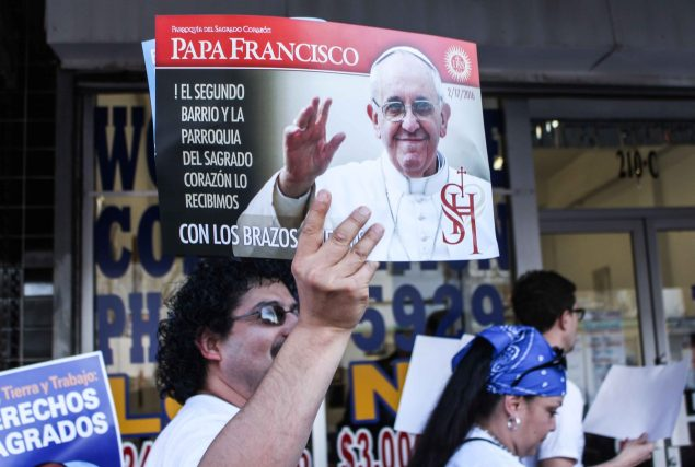A man holds a welcome sign for Pope Francis. (Maria Esquinca)