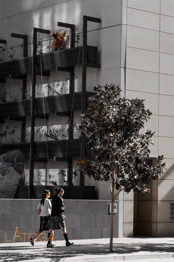 A Landscape Worker appears to hover over two girls walking down Mission Street in San Francisco, California