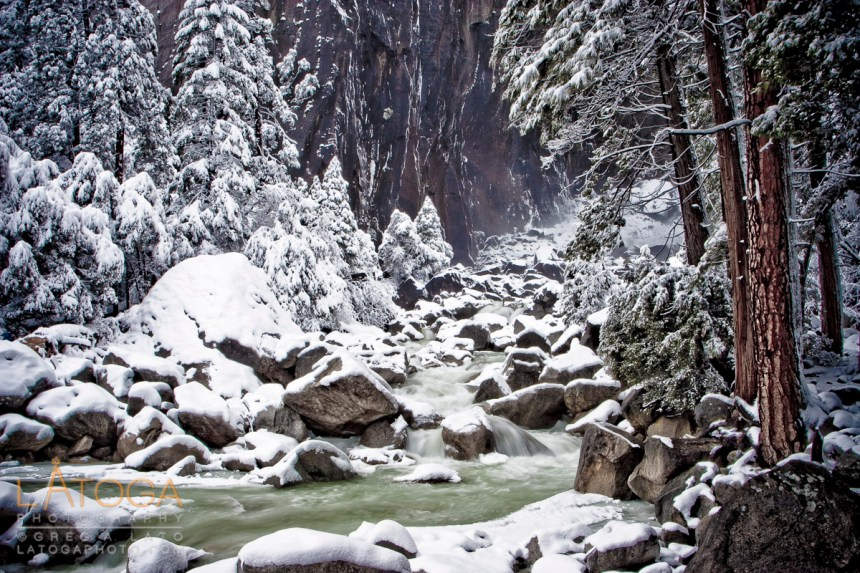 Yosemite River winds past snow covered trees and boulders at the base of Yosemite Falls in Yosemite National Park after winter storm.