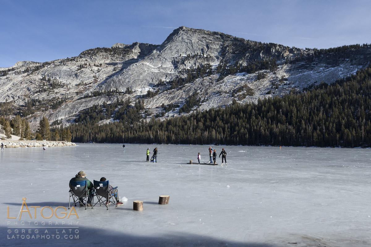 Visitors ice skating and enjoying novalty of accessing frozen Tenaya Lake in Yosemite National Park, California, January 2012.
