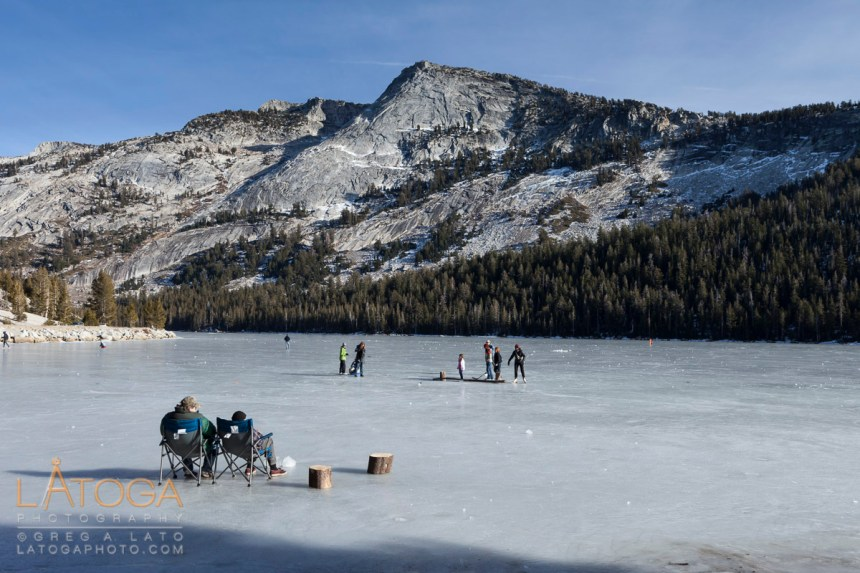 Visitors ice skating and enjoying novalty of accessing frozen Tenaya Lake in Yosemite National Park, California, January 2012.