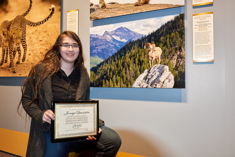 Jenaya Launstein from Pincher Creek, Alberta poses beside her award-winning image, Ramscape, on exhibit in the Smithsonian National Museum of Natural History in Washington, DC. Photographed in Waterton Lakes National Park, Alberta, Canada.