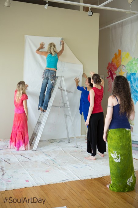 It takes a team of artists to hang a canvas.