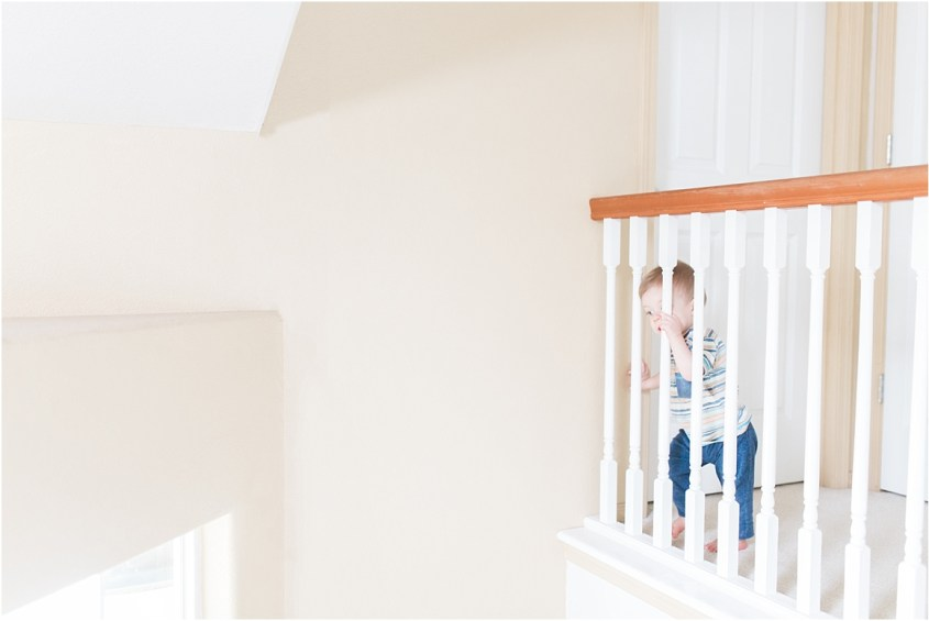 One year old looking out over landing | Laura Ryan Photography
