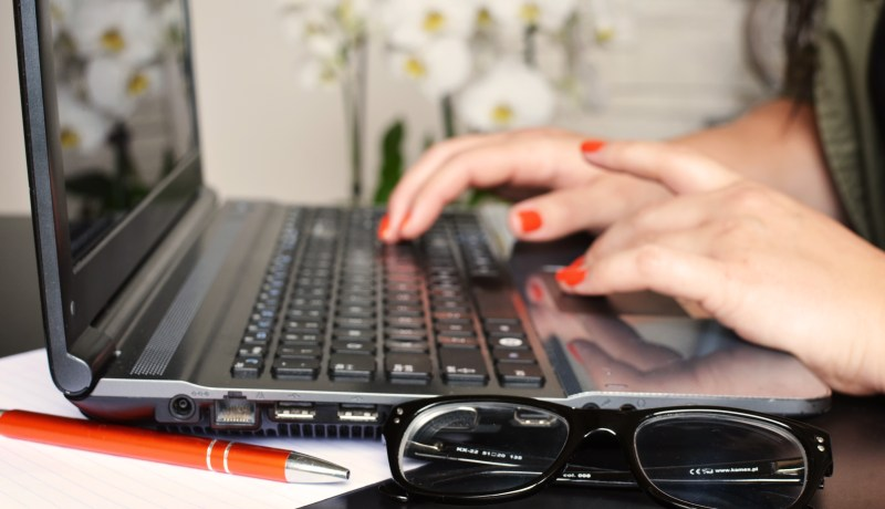 woman working at a laptop. Does your business blog need some of your time?
