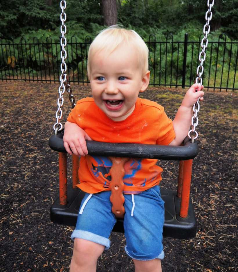 Bodhi at 15 Months - Bodhi swinging on the swings in an orange t-shirt