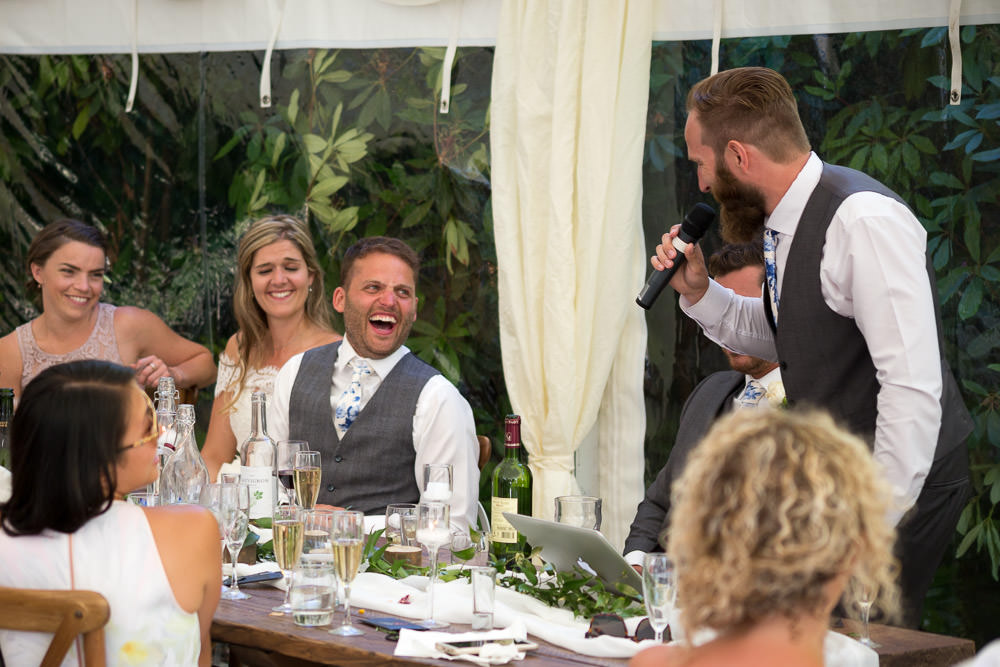 top table laughs during best man's speech at Tros Yr Afon wedding venue, DIY Beaumaris castle wedding