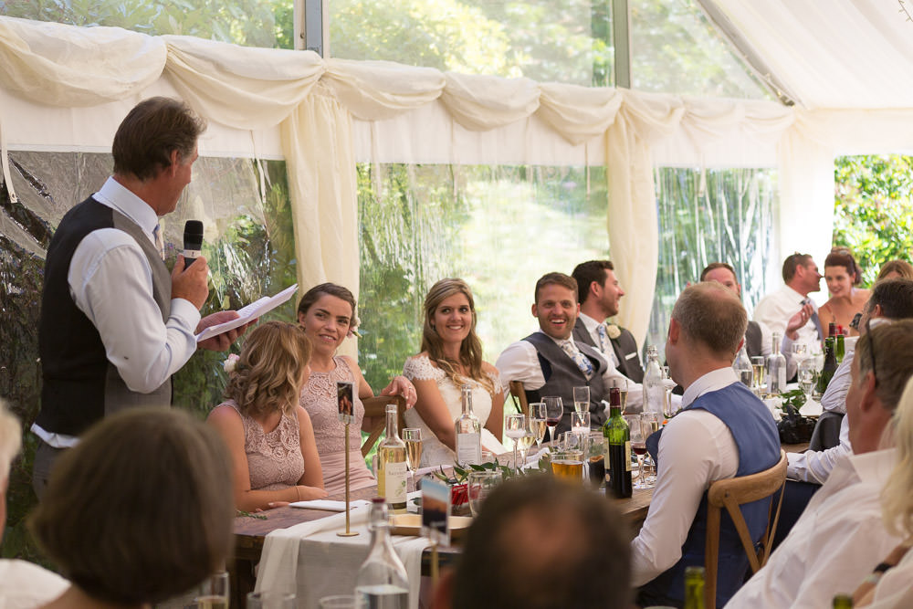Top table laugh at father of the bride speech at Tros Yr Afon wedding venue, DIY Beaumaris castle wedding
