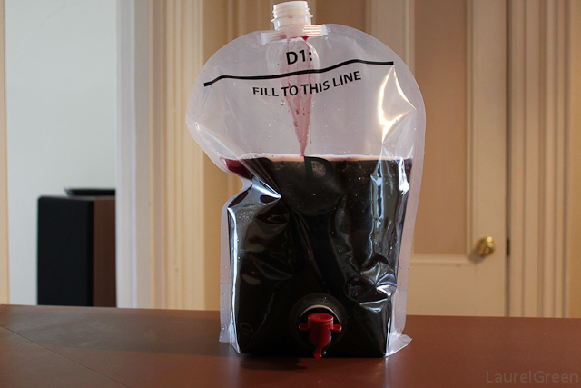 a photo of red grape concentrate added to a fermenting pouch