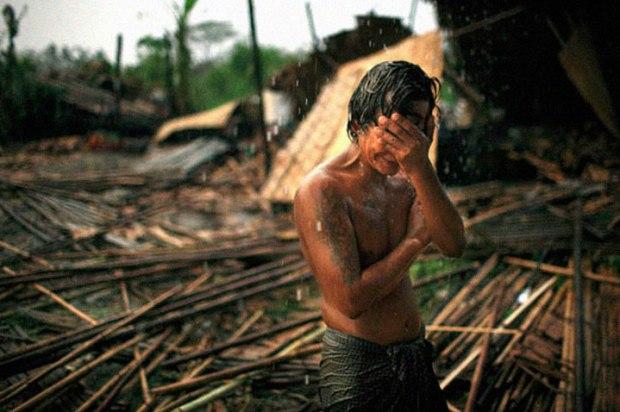 Hhaing The Yu se tenant la tête sur les vestiges de sa maison emportée par l'ouragan Nargis en Mai 2008 (Birmanie)