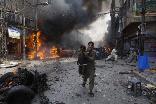 Un homme porte un enfant pour l'emmener loin du lieu d'un attentat à la bombe au Pakistan