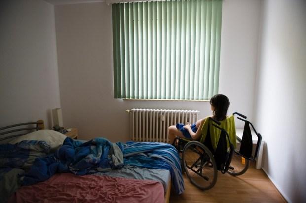 Jenny assise dans un fauteuil roulant devant une fenêtre. Elle pèse environ 50 kg, Dirk utilise un fauteuil roulant pour la déplacer dans l'appartement. Les chambres sont toutes plongées dans l'obscurité pour que les voisins ne puissent pas voir à l'intérieur et découvrir la poupée. « C'est dommage que je ne puisse pas sortir avec Jenny. Des fois, j'aimerai en faire plus… »