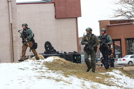 Law enforcement officers sweep the area outside of a King Supers grocery store, which was the site of a shooting in Boulder, Colorado, U.S. March 22, 2021. REUTERS/Kevin Mohatt
