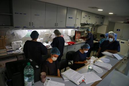 ACOMPAÑA CRÓNICA: URUGUAY CORONAVIRUS - AME081. MONTEVIDEO (URUGUAY), 15/04/2021.- Enfermeros del área del Centro de Tratamientos intensivos (CTI) del hospital privado Casmu atienden a pacientes covid-19, el 14 de abril de 2021 en Montevideo (Uruguay). El silencio ensordecedor, el aislamiento, la soledad y los últimos impulsos por intentar evitar que se escape una vida más. Esta es la rutina de las últimas semanas para los trabajadores de cuidados intensivos en el Casmu, uno de los hospitales privados de Uruguay. El impactante relato de ese personal sanitario, que lucha a diario por que la respiración artificial que reciben sus pacientes no sea la última de sus vidas, se ve en los pasillos y sectores de cuidados intensivos (CTI) de este hospital al que tuvo acceso Efe. EFE/ Raúl Martínez