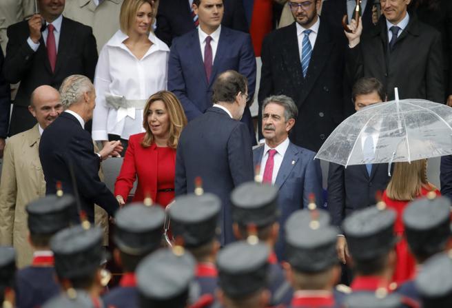 El presidente del Gobierno en funciones, Mariano Rajoy (c), saluda al presidente de Cantabria, Miguel Ángel Revilla, a su llegada al acto central del Día de la Fiesta Nacional.