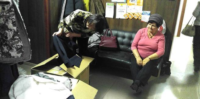 Una mujer examina la ropa donada para los desplazados en Irpin