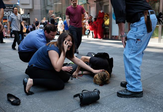 Tres transeúntes asisten a un hombre que fuer herido durante el atropello