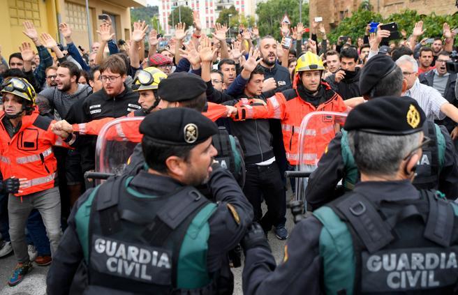 Bomberos hacen un cordón de seguridad para proteger a los concentrados ante el colegio electoral en Sant Julià de Ramis