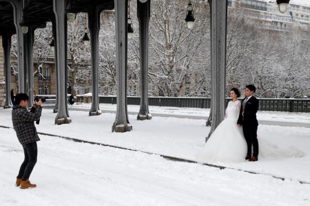 Una pareja de recién casados se hace fotografías en un puente de París