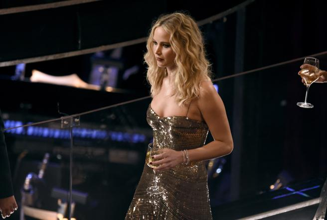 La actriz ha ido a buscar su lugar en el teatro sin dejar en ningún momento su copa de vino.