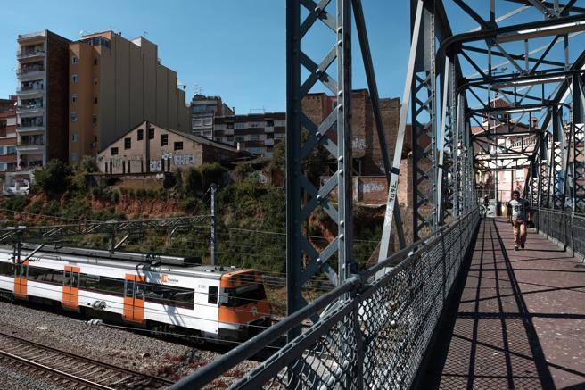 Imagen de un tren de Rodalies a su paso por un puente cerca de la estación de metro de Santa Eulàlia a pocos metros de la zona donde las vías se cubrieron en Sants.
