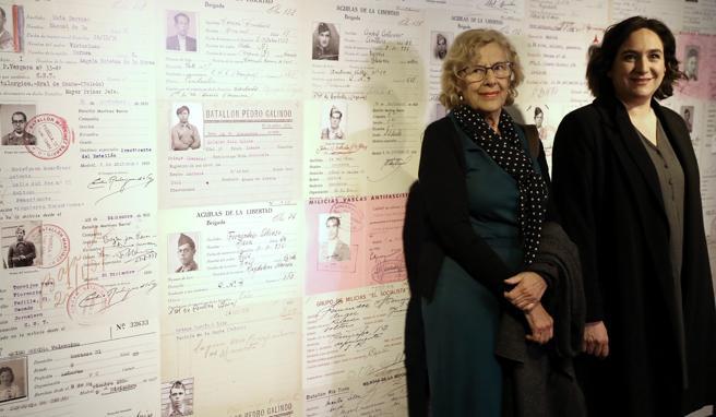 La alcaldesa de Madrid, Manuela Carmena (i), y de Barcelona, Ada Colau, posan junto al cartel regalo de la ciudad de Barcelona a la exposición madrileña