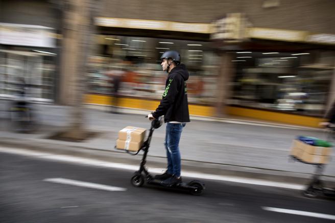 Un hombre subido en un patinete eléctrico reparte paquetería en Barcelona