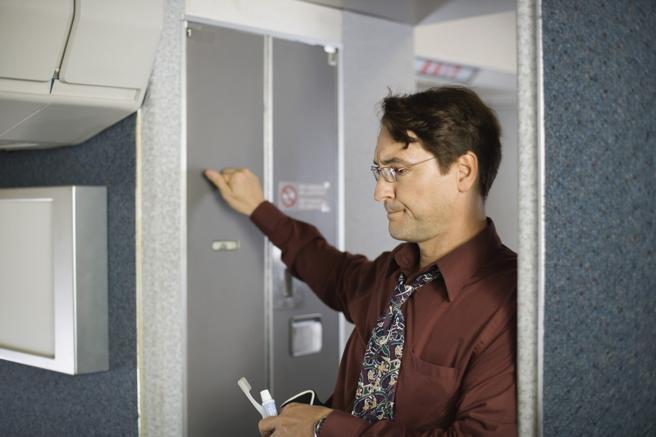 Un pasajero llamando a la puerta del baño de un avión