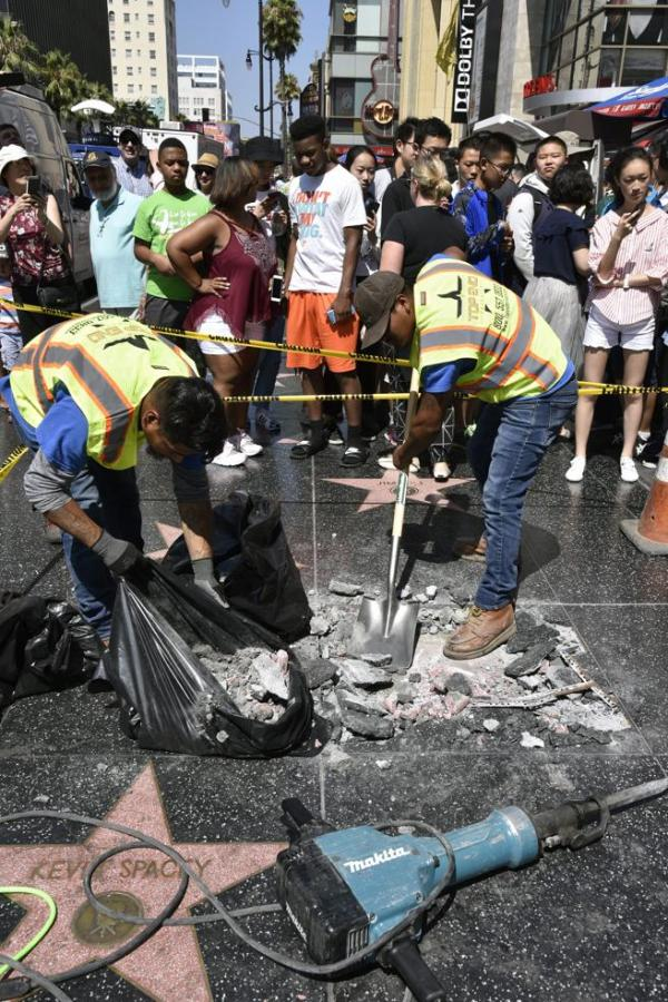 Un grupo de trabajadores retiran los restos dañados de la estrella del presidente estadounidense, Donald J. Trump, tras que fuera destruida durante la noche