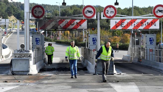 Trabajadores del grupo de construcción francés Vinci en un peaje donde se puede leer 'Macron dimisión' cerca de Marsella.