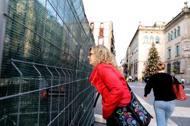 Una ciudadana observa el pesebre tras las vallas