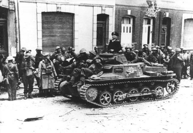 Prisioneros de guerra británicos junto a un tanque ligero alemán.