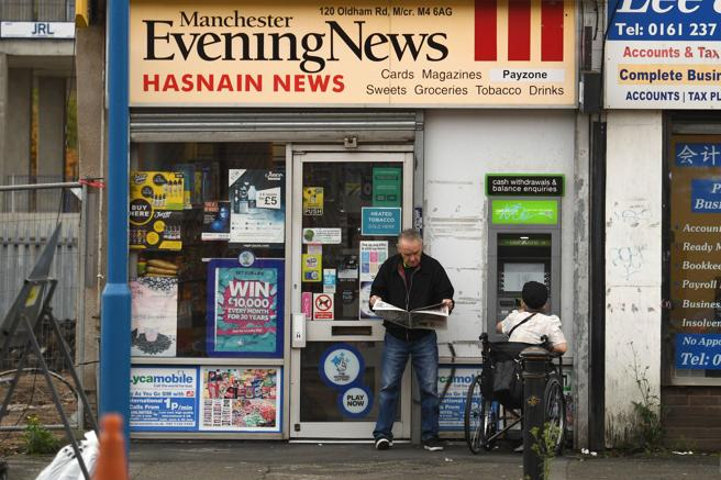 A man without a mask reads a newspaper outside a shop in Ancoats, north Manchester.