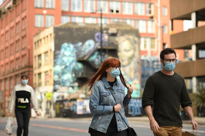 Passers-by with masks on a Manchester street.