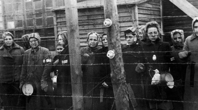 Prisioneras tras la alambrada del campo de Ravensbrück (1945)