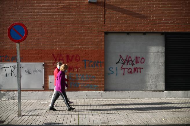 Dos personas pasan al lado de las pintadas ubicadas en el lugar donde se inició una disputa que terminó con la vida de Iván