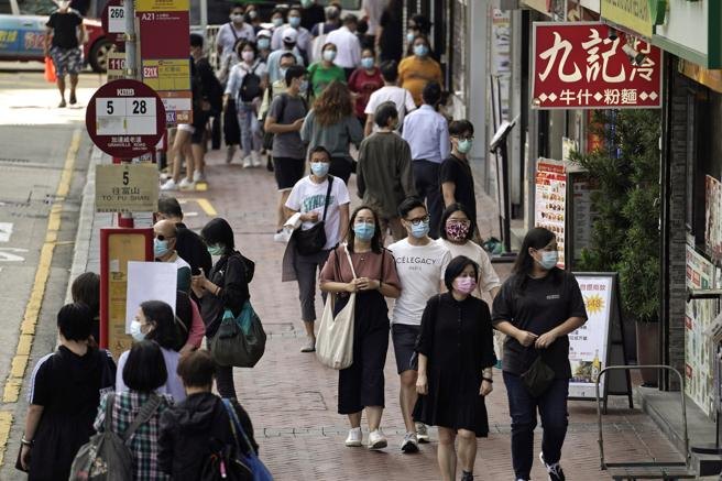People wearing face masks to protect against the coronavirus walk down a street in Hong Kong, in an October photo