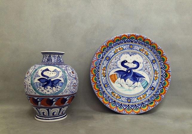 vaso e piatto in maiolica con uccelli dal collo intrecciato