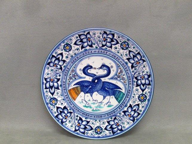 piatto in ceramica con astorri dal collo intrecciato