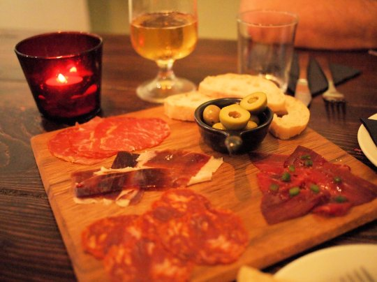 A platter of mixed cured meats with olives and crusty bread