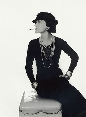 Coco Chanel models one of her Little Black Dresses with the Obligatory strings of Pearls!