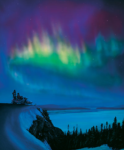 The Northern lights over snow and icy water