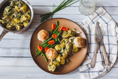 Pollock fish cakes with summer potato salad and green beans