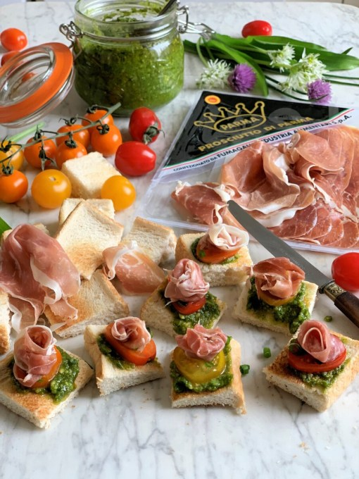 Tear or cut each slice of Parma Ham in half lengthwise, and roll each long slice up into a rosette shape. Place the Parma Ham rosette on each loaded crostini and place them on to a serving platter.