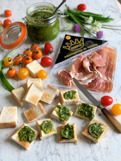 Toast the bread and cut each slice into 9 squares, to make 18 crostini. Spread half a teaspoon of pesto onto each square of toast.