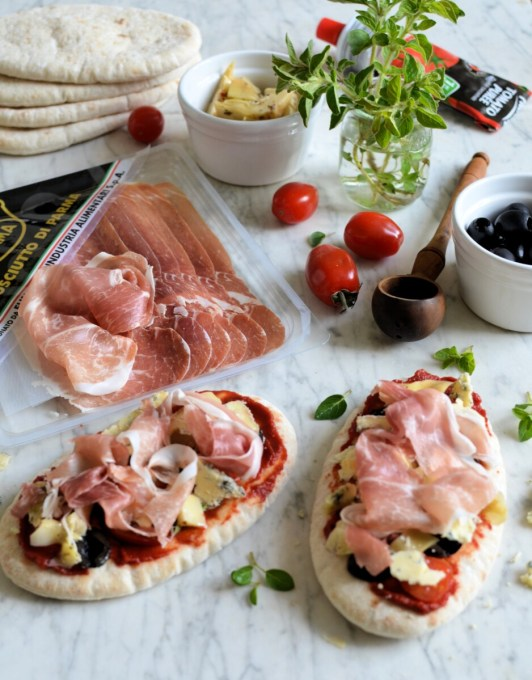 Tear the Prosciutto di Parma ham into pieces and pile it into mounds on top of the cheese and other toppings. Drizzle some of the oil from the artichokes over the the ham.