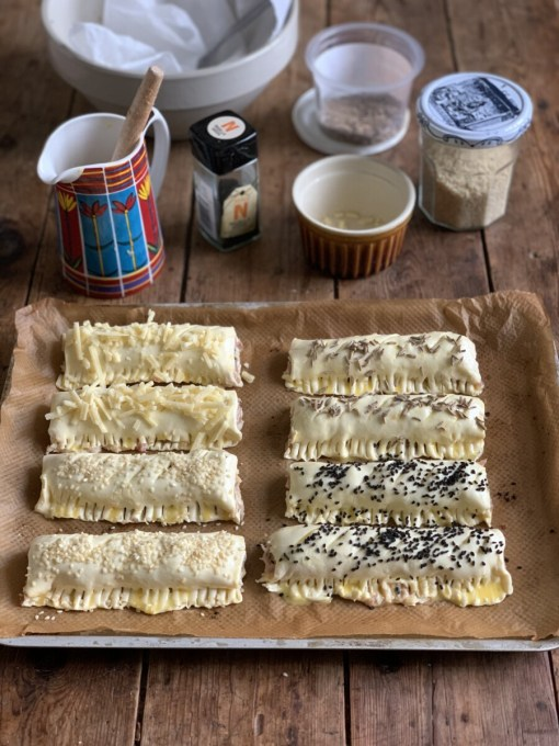 Brush the sausage rolls with the beaten egg, then sprinkle any toppings you may be using over the tip, such as nigella seeds, sesame seeds, fennel seeds and extra grated cheese.